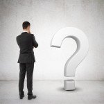 businessman looking at white question mark symbol