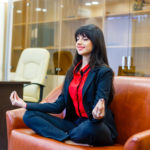 Successful business person meditating in yoga pose during business day.